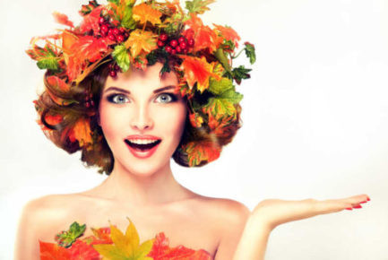 Autumn Beauty - fashion Makeup With Red and yellow autumn Leaves on  girl head . Emotions and surprise on the face of the autumn girl
